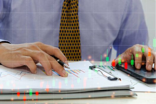 Business man holding pen, business documents, reports, graphs and charts of financial statements and profit growth.Stocks Exchange Market Graph Concept.