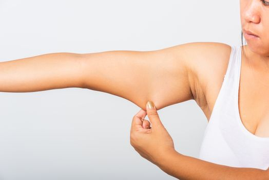 Close up of Asian woman pulling excess fat on her under arm, problem armpit skin