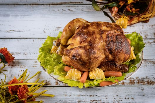 Thanksgiving Day roasted chicken Thanksgiving table served with decorated bright autumn leaves on table setting.