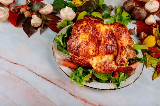 Autumn traditionally decorated table with traditional Thanksgiving dinner in the roasted chicken with harvest holiday