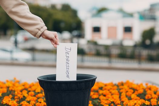 Woman throws sheet with word depression into trash can. Psychology help