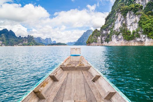 Wooden Thai traditional long-tail boat on a lake with mountains at Ratchaprapha Dam or Khao Sok National Park, Surat Thani Province, Thailand