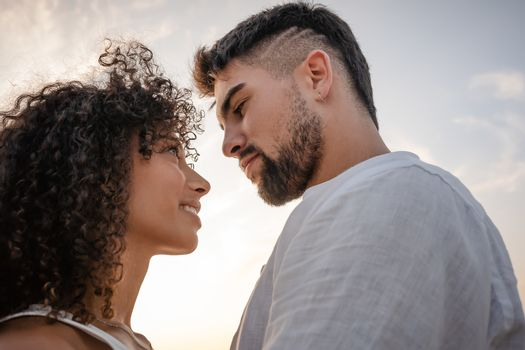 Side view of two young multiethnic passionate lovers looking in the eyes each other - Macho bearded sexy man looks at his Latin woman with ardor in a romance sunset scene ideal for a book cover