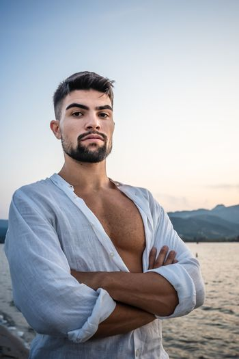 Strong attractive muscular caucasian bearded man looks serious at the camera with white shirt open and strong chest with the pectoral - Portrait of male sexy young model with deep and intense gaze
