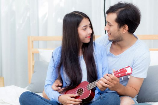 Young Asian couple playing ukulele relaxing with happiness and joyful in bedroom.