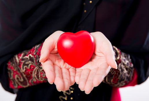 hand of young asian muslim woman holding red heart shaped pillow closeup isolated on white background.