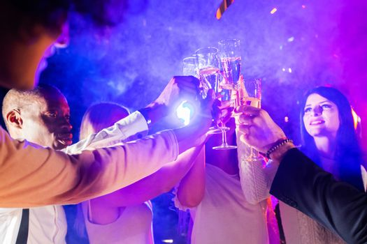 New year celebration party, holidays, nightlife and people concept - smiling friends clink glasses of champagne in night club