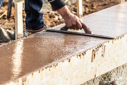 Construction Worker Using Wood Trowel On Wet Cement Forming Coping Around New Pool.