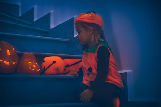 Cute Little Baby Dressed as Festive Little Pumpkin Decorating Home with Carved Gourds Lanterns. Preparation to Halloween Party.