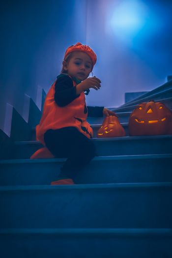 Cute Little Baby Dressed as Festive Little Pumpkin Decorating Home with Carved Gourds Lanterns. Decor for Halloween Party.