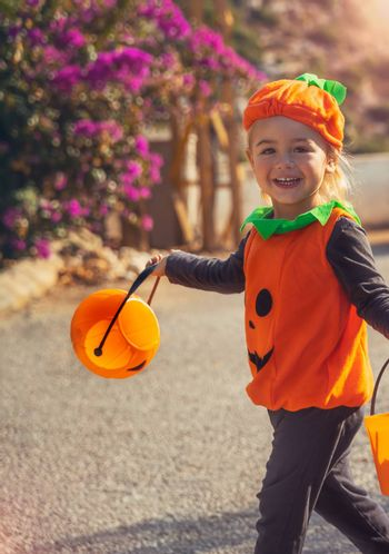 Halloween Celebration. Nice Little Baby Dressed in Pumpkin Character Outfit On The Way to Collect Candies from the Neighbors. Kids Enjoying Happy Autumn Holiday.