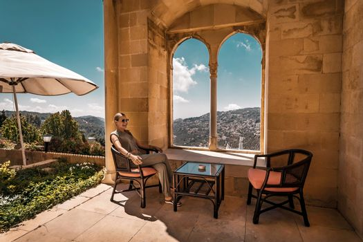 Happy Woman on the Open Terrace with View on Beautiful Mountains. With Pleasure Spending Time in Travel. Enjoying Summer Vacation.