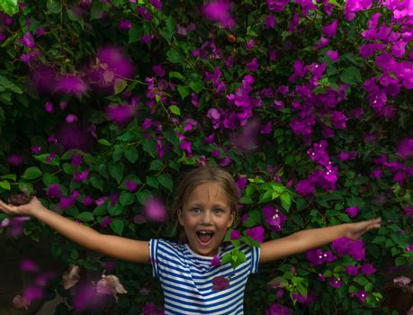 Portrait of a Little Cheerful Girl in Beautiful Floral Background. Happy Child with Raised up Hands Enjoying Freshness and Beauty of Blooming Garden.