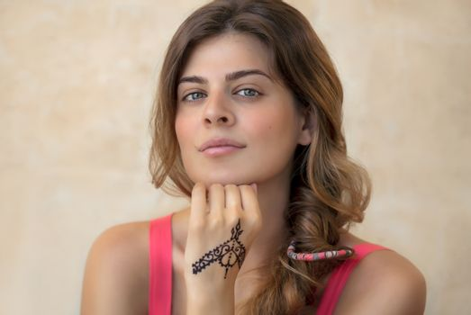 Portrait of an Attractive Woman Isolated on Beige Background with Beautiful Henna Drawing on the Hand. Stylish Body Art. Authentic Beauty of Young Female.