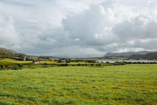 Beautiful scandinavian landscape with village, meadows, mountain