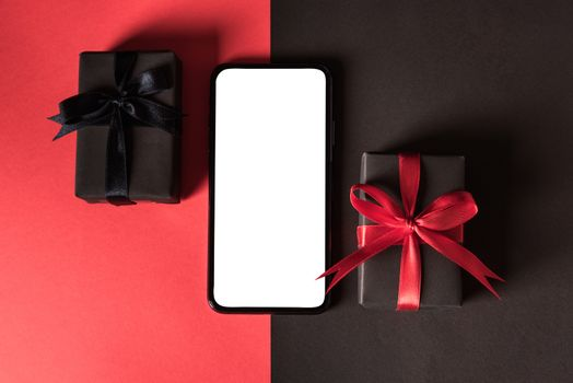 Black Friday sale shopping concept, Top view of gift box wrapped in black paper and black bow ribbon and modern mobile smartphone, studio shot on red and dark background