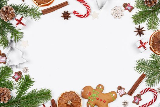Christmas frame of decor on white, fir tree, gingerbread cookie and dandy canes on white background