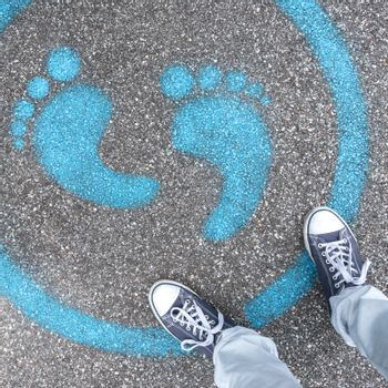 Man standing on blue dot. Sign painted on the pavement reminding users to maintain a physical distance of 3 feet / 1 meter during the COVID-19 pandemic.