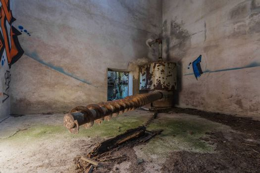 rusty long spindle in a tower of a factory