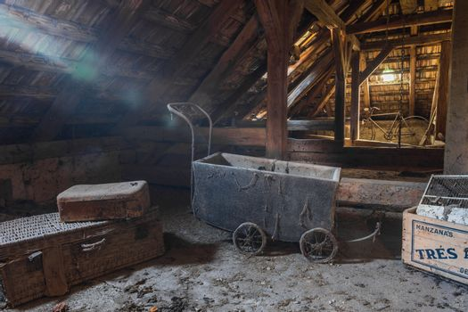 Old stroller with light on a loft in a house