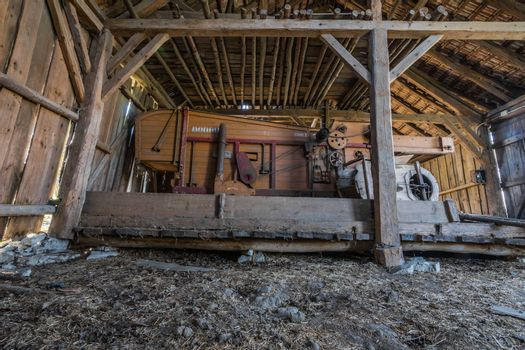 old wooden threshing machine in abandoned house