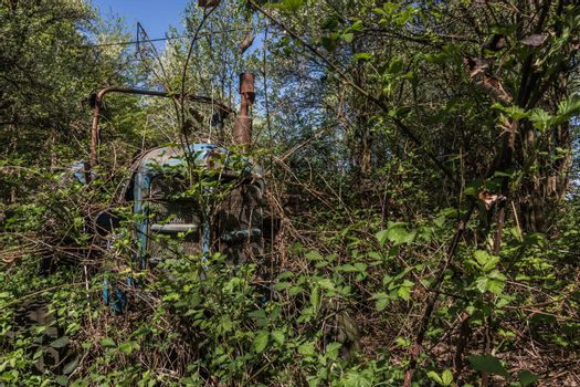 faded blue tractor in the forest front view