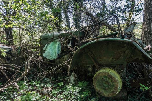 old overgrown green tractor at a farm