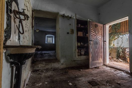 sink and open wooden door in an abandoned house