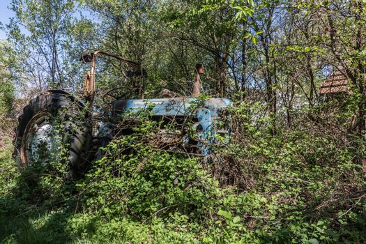 old blue overgrown tractor on a farm