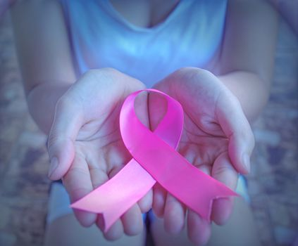 The concept of health care and breast cancer encouraging people around the world of breast cancer patients. Close up holding pink ribbon breast cancer awareness day.