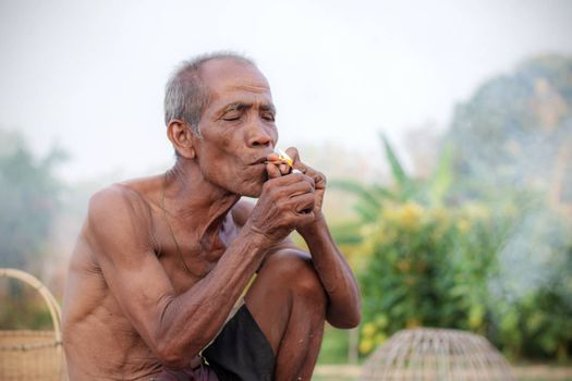Older people are smoking in the countryside.