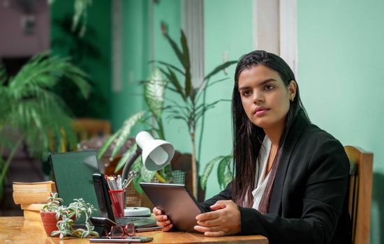 Young woman with long black hair sitting at a working desk with a tablet in her hands.