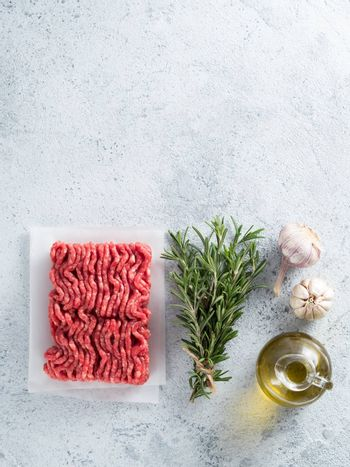 Fresh raw minced beef, fresh rosemary, garlic, olive oil on backing paper over light gray cement background with copy space. Top view or flat-lay.