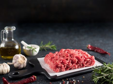Fresh raw minced beef on backing paper and cutting board and ingredients over black cement background with copy space.