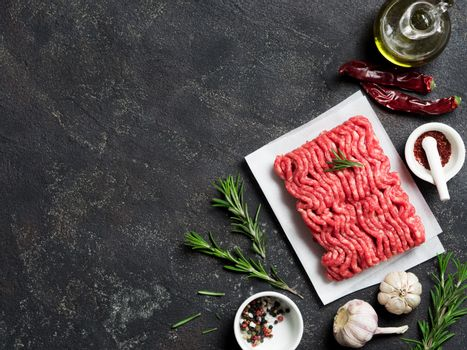 Fresh raw minced beef on backing paper and cutting board and ingredients over black cement background with copy space. Top view or flat-lay.