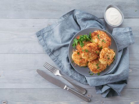 Close up view of potato pancakes. Potato flapjack on gray plate over gray wooden table, with fresh parsley and sour cream. Copy space for text. Top view or flat-lay.