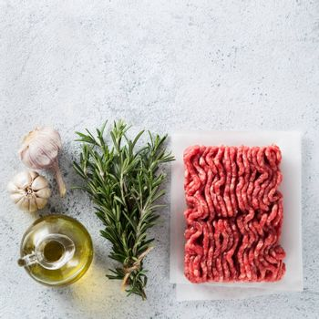 Fresh raw minced beef, fresh rosemary, garlic, olive oil on light gray cement background with copy space. Top view or flat lay. Cooking ingredients concept. Square shape