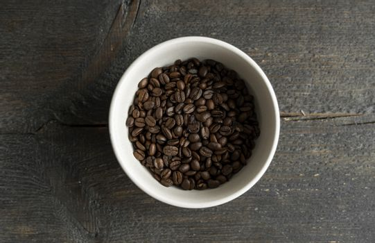Bowl filled of fresh arabica or robusta coffee beans on a wooden table.
