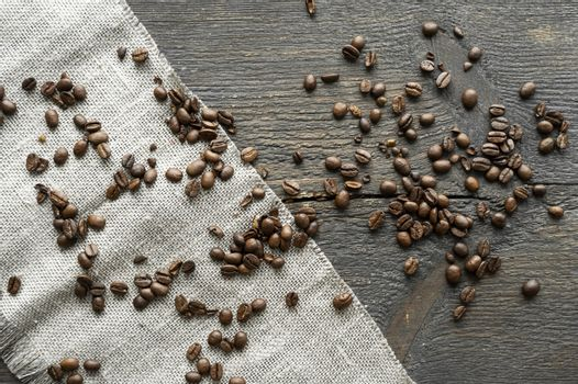 Scattered fresh arabica coffee beans on a linen textile and wood table.
