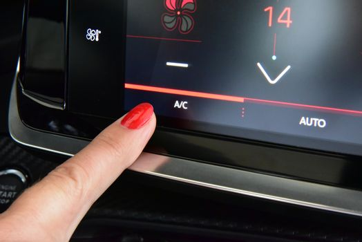Female finger on the button to activate the air conditioning in the car