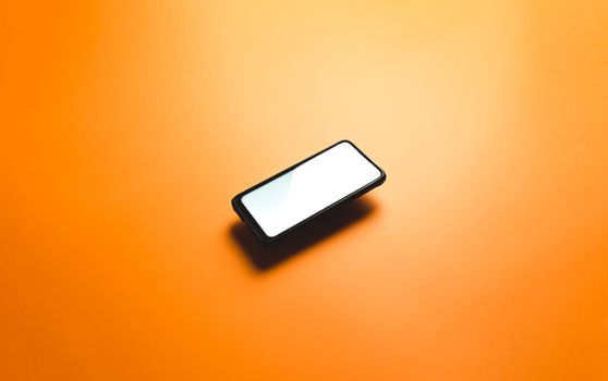 Minimalistic mock up flat image design with a floating mobile phone with copy space and white scree to write over it over a flat orange background
