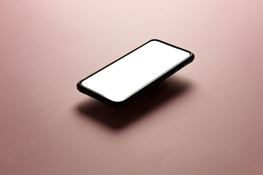 Minimalistic mock up flat image design of a mobile phone with copy space and white scree to write over it over a flat pastel pink background