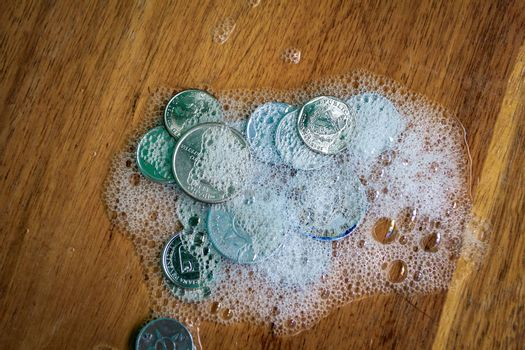 Group of coins covered in foam on a wooden surface