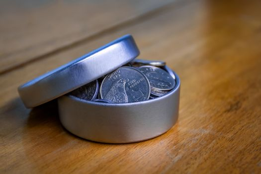 Open silver container filled with coins on a wooden table and an unfocused background