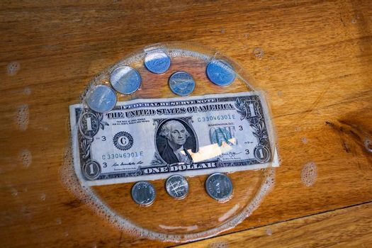 A one dollar bill and coins, all covered by a big bubble