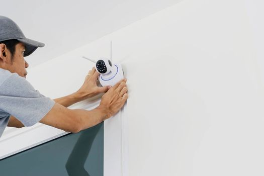 Technicians are installing a wireless cctv camera on the wall, can connect to the Internet, and control the camera via a smartphone or tablet.