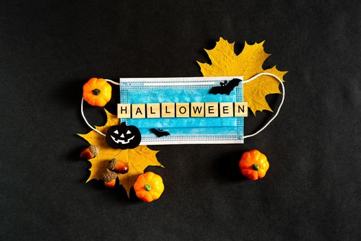 Halloween pumpkins, protective medical mask and yellow maple leaves on a black background, bats made of black paper. The inscription HALLOWEEN The concept of Halloween and covid-19. Flatlay.