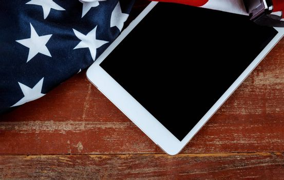 U.S national flag and screen e-tablet on wooden boards