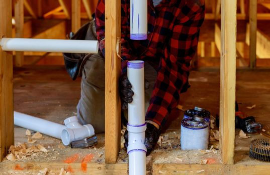Plumber installing primer and glue PVC pipe at construction new home
