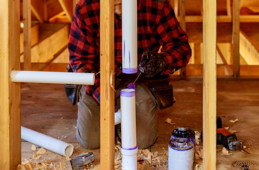 A Plumber applying primer and glue a PVC pipe drain assembly in under construction